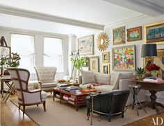 A salon-style display of art makes a colorful statement in the living room. The wing chairs, from Privet House, and the sofa are upholstered in a Holly Hunt linen; the walls are painted in Farrow Ball's Cornforth White. Architectural Digest, Cornforth White Living Room, My Living Room, Living Spaces, Style Salon, Stained Table, Manhattan Apartment, New York City Apartment, Farrow Ball