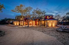 A mulched yard and stone siding give this home a beautiful, rustic look. A lighted walkway leads to wooden columns that frame the front entrance. Trees provide height and interest in the front yard.