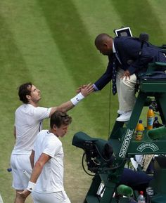 Andy Murray of Britain, left, and Tomas Berdych of the Czech Republic shake hands with the umpire after Murray won their men's semifinal singles match on day twelve of the Wimbledon Tennis Championships in London, Friday, July 8, 2016. (AP Photo/Tim Ireland)