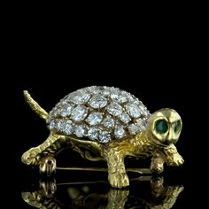 A flashy diamond turtle with a funny face that only a mother turtle could love. He or she is well protected by a shell containing fifty two sparkling, high quality, round brilliant diamonds totaling about 5.00 carat. Two emeralds make up its bright wide eyes. 18k yellow gold.