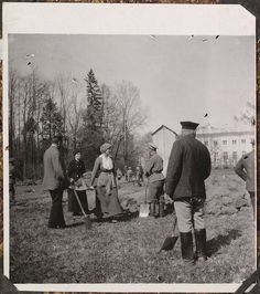 Grand Duchess Tatiana and Tsar Nicholas II (both center) during captivity working in their garden on the grounds of Tsarskoe Selo-their palace standing in the distance.