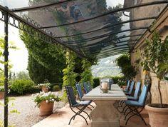 un style méditérranéen, pergola en fer forgé et une longue table avec des chaises