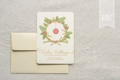 Weihnachtskarte mit Golddruck. DIN A6-Karte mit abgerundeten Ecken und cremefarbenem Papier. Weihnachtskarte mit Kranz aus Ilex/Stechpalme und Chritsbaumkugel in Grün und Rot. Auf Wunsch mit Adressetikett. ©passion4paper www.die-edle-karte.de