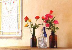 Rosas de diversas cores enfeitam as simples garrafas espalhadas pelo rústico aparador  Rogério Voltan / Casa e Jardim