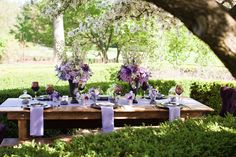 this table setting combines woody, rustic elements with a more formal setting of purples, mauves and black. interesting and rich colour combination.