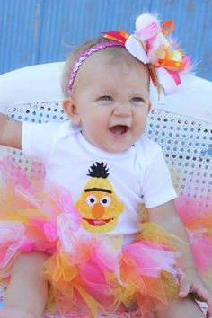 Bert onesie with name, orange, yellow, and pink tutu, and matching hair bow with rhinestone and feathers on Etsy, $38.00