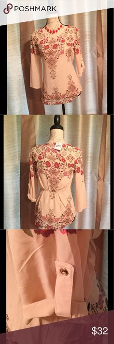 Floral print top. Optional rolled arm cuff. Floral rose/cream print top with sleeves that can be rolled and cuffed with button (see photos). Elastic detail at back ways. Slightly sheer material. 100% polyester. Machine wash/line dry. Break in pattern is part of the normal design (see photos). Necklace not included. New never before worn. This is an NWT boutique item. No trades please. I offer a bundle discount. Thanks for visiting my closet! WILA Tops Tunics