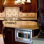 Juparana Golden Vyara Granite with the microwave under the island.