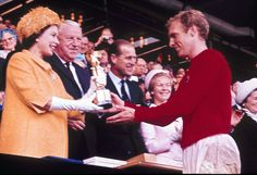 63 pictures of Queen Elizabeth II from every single year of her record reign - Business Insider - 1966: Queen Elizabeth II presents the World Cup, the Jules Rimet trophy, to England's team captain Bobby Moore, July 30, 1966. This was the first and only time England has ever won the World Cup.