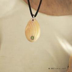 Olivín+v+bílé+Do+amuletu+z+kosti+je+do+stříbra+zasazený+broušený+olivín,+kost+je+zdobená+jemným+vzorem.+Ke+šperku+je+kožená+šňůrka+a+dřevěná+krabička.+Materiál:+Ag+925/1000,+hovězí+kost,+olivín+Váha:+9,8+g+Rozměr:+4,4+cm+x+2,4+cm