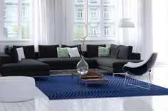 Bright airy modern living room interior with white walls and wooden floor, large windows with filmy drapes, and a simple rug and corner unit modular settee in charcoal grey. Living Room Interior, Living Room Decor, Living Rooms, Traditional Sofa, White Throw Pillows, Grey Furniture, World Of Interiors, White Walls, Decoration
