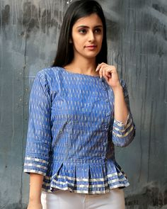 Shop online Jade blue ikat peplum top A peplum with the right twist of ikat. Contrast white ikat stripes on the sleeve and on the subtle frill of the top. Buttons are stylishly placed on slightly one side in an overlap fashion. Short Kurti Designs, Kurta Designs Women, Peplum Top Pattern, Peplum Tops, Peplum Top Outfits, Short Tops For Jeans, Cotton Tops For Jeans, Crop Top Designs, Blouse Designs