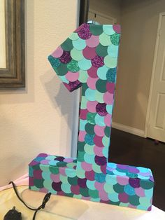 "Giant #1 for my daughter's upcoming mermaid themed 1st birthday party. Cut out cardboard, made the 3D # and glued together. Then glued different colored paper circle to create the ""scales""."