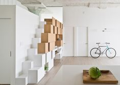 Irregular-shaped boxes have been grouped together to create storage, a study, and stairs up to a mezzanine play area in this renovated loft.