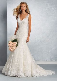 Modern fit and flare wedding dress of chantilly lace and tulle over satin with sheer straps and a low V-shaped neckline. The gown has been decorated throughout with hand-placed cotton embroidered lace and sequin beading. The gown is finished with a plunging back neckline, matching self-covered buttons and a chapel length train.