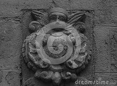 Shot in black and white, detail on the sculpture on the facade of this historic building representing an angel character. Set in Lleida, Catalunya, Spain, Europe