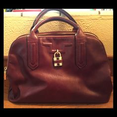 """Burgundy Satchel Bag with Strap I am selling a beautiful burgundy satchel purse. It has 3 zipper compartments. It has an inside zipper pocket and a cellphone pocket. It is 100% vinyl. There is also an adjustable strap. The measurements are 9.5"""" h X 15.5"""" l. Avenue Bags Satchels"""