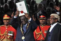 President Mwai Kibaki (2ndL) lifts up Kenya's new constitution soon after promulgating it at the Uhuru Park grounds on August 27, 2010 in Nairobi. FILE PHOTO   TONY KARUMBA