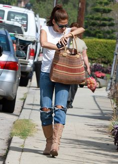 Eva Mendes street style. holes in the jeans with mid calf boots. plus vintage one of a kind tote bag.
