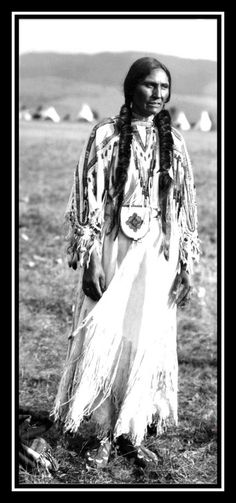 Mrs. John Bushman, a Salish woman on the Flathead Indian Reservation in western Montana. A group of teepees is in the distance at the base of a ridge of mountains. Photographed c. 1905.