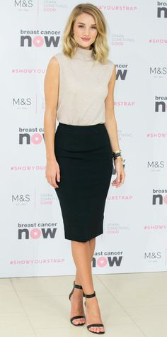 Rosie Huntington-Whiteley celebrated the launch of her new Marks & Spencer lingerie range that will benefit Breast Cancer Awareness in an oatmeal sleeveless turtleneck knit tucked into a sharp black pencil skirt, with black ankle-strap sandals.