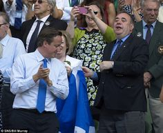 Whatsupic - I'm Just Supporting Andy, Honest! Scotland's First Minister Alex Salmond Raises Giant Saltire Behind David Cameron's Head in Royal Box on Centre Court