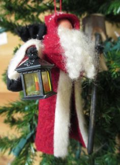 New in 2014, our Old World Santa has the feel of an old European traveler. He wears an under coat of green with a long red cloak lined in off-white fur. He carries a small miniature lantern in which weve inserted a hand painted wooden candle. A lumpy sack of black homespun is on his shoulder, and a long walking stick in his other hand. A light dusting of snow is on his shoulders and hood.  NOTE - Lantern styles vary between two - and may be square (as shown) or round.  Add an optional doll…