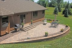 A raised patio created with a retaining wall units and a paving stone surface is a stunning, low-maintenance solution for an aging, high-maintenance wooden deck.