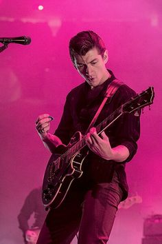 Alex, with his guitar, and pink smoke.