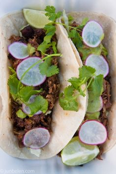 Sisig tacos: lime and soy marinated, fried pork cheek and shoulder meat with shredded lettuce, finely sliced radish, and salsa verde on corn tortilla