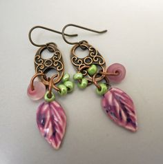Expand your fall wardrobe colors with these purple leaf earrings. The cermic leaves were handmade by me and the color was inspired by the big maple tree in our front yard, whose leaves were turning purple and pink, with magenta colored veins.  The matte pink glass dangles are also artisan made and are accented with small, shiny green glass beads. The decorative copper links add to the artisan look. The Purple Leaf earrings hang from brass earwires.
