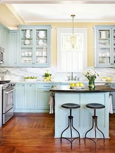 Robins egg blue is a fun departure from white cabinets and contrasts well with the dark floors, carrera marble and yellow walls.