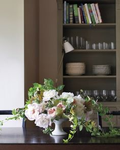 """High Season  """"This arrangement is inspired by that time in June when there are so many fragrant things coming out outside and flowers are turning into fruit,"""" Ngo says of the peonies, roses, blueberries, and honeysuckle draped over a low, footed urn."""