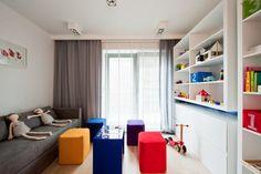 I w tym pokoju pojawiają się ultramarynowe akcenty np. niewielkie, połyskliwe biurko. Kolorem dominującym pozostaje biel - białe są szafy do zabudowy, drewniane żaluzje na oknie i regał z półkami i szufladami wykonany z lakierowanego tworzywa. Akcentem kolorystycznym są pufy