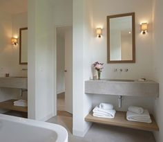 Belgian modern bath with concrete vanities...