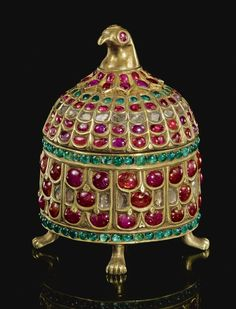 AN INDIAN GEM-SET GILT-METAL CASKET WITH BIRD-HEAD FINIAL, INDIA, 19TH CENTURY  of domed cylindrical form, wholly set with cut rubies, emeralds and diamonds, the four short feet designed as animal paws, the finial in the form of a parrot or falcon head, the cover fitted to the base with twist-lock opening smoothly to reveal plain interior 7.5cm. height 5cm. diam.