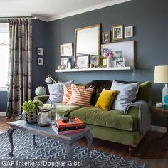 Die grau-blaue Wand verleiht dem Wohnzimmer Charakter. Das gemütliche Stoffsofa in Grün und die Bilderrahmen darüber machen den Raum schön wohnlich. Der  …