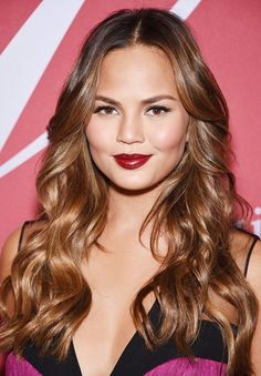 Chrissy Teigen stuns with gorgeous, wavy locks and red, vampy lipstick.