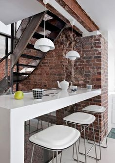 Exposed brick wall, partially exposed ceiling, metal industrial staircase. I love how the brick and patina metal of the staircase is set off by all that modern white. Great to tuck the island table right under the stairs like that.