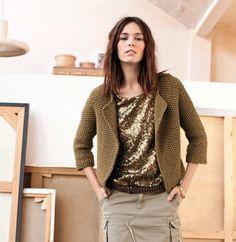 La veste courte en point de riz, sans finitions. Modèle ultra mode avec sa couleur olive et sa ligne brute, on la porte ouverte avec un revers de col.