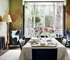 Stefano Pilati's eclectic Paris dining room's woodland mural, painted by Mathias Kiss and Olivier Piel of Atelier Attilalou, artfully echoes the garden, which was landscaped by Louis Benech.
