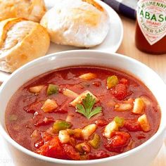 Gazpacho in white bowl on wood surface with dinner rolls and Tabasco bottle