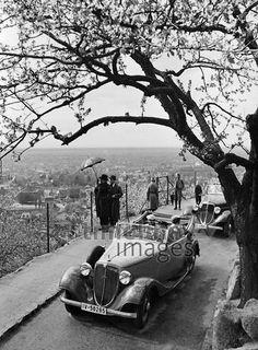 Urlauber bewundern die Aussicht, 1936. Ausflügler sind aus ihren Autos ausgestiegen und betrachten von einem erhöhten Punkt aus die Aussicht auf eine Stadt. Timeline Classics/Timeline Images #30er #1930er #Ausflug #Aussicht #Auto #Freizeit #Oldtimer