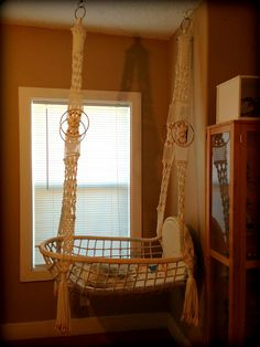 Hanging Baby Bassinet...love! Wicker chair turned sideways with macrame...great idea!