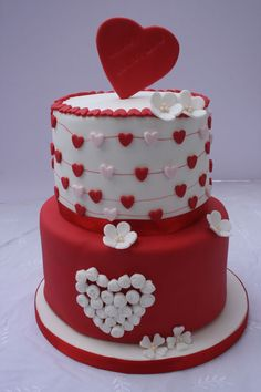 Two tiered birthday cake for girls who wanted a Valentine's theme. The bottom cake is chocolate fudge and the top tier is lemon with ho...