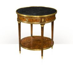 5005-589 A cerejeira lamp table with fine brass mounts, the brass bound white veined black marble circular top, above a frieze drawer on turned and fluted legs joined by a circular undertier. The original Louis XVI. W 26 x D 26 x H 28