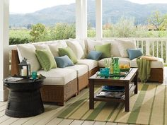 This country-style porch enjoys sweeping views of the mountains in the background and provides comfortable seating for guests. Blue and green accent pillows add character to the sectional and a subtle striped rug anchors the space. Front Porch Furniture, Small Patio Furniture, Garden Furniture Design, Best Outdoor Furniture, Patio Furniture Sets, Furniture Ideas, Furniture Layout, Street Furniture, Modern Furniture