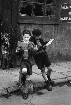 U.K. Two boys engrossed in their comic books, May 17th, 1952. // Thurston Hopkins