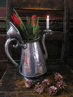 Pewter coffe pot. Used as a flower vase.  Nice christmas decor in my home.