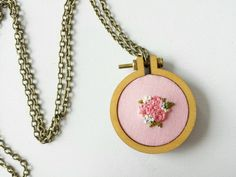 Pink Floral Embroidery Hoop Necklace  Handmade embroidery hoop necklace featuring dark pink flowers stitched on light pink fabric. The pendant